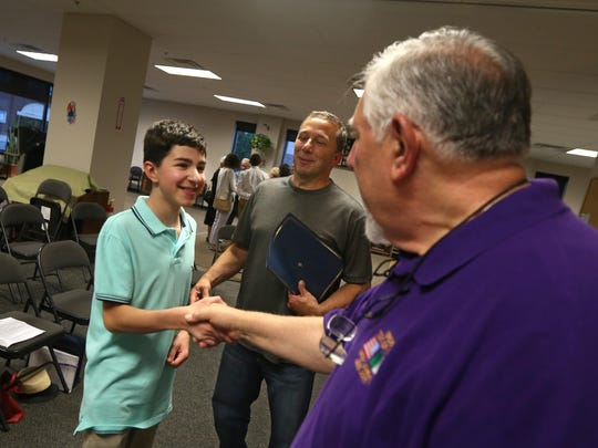 Michael Salamone, 14, Greece, gets a congratulatory handshake from Order Sons of Italy in America member Tom Meleca of Walworth for his essay that won a prize in a contest put on by the organization.