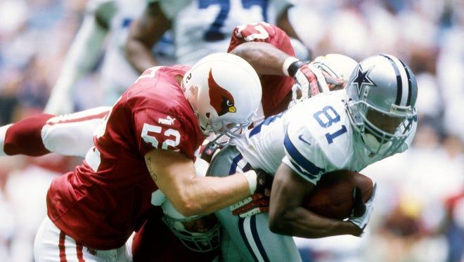 Arizona Cardinals defensive back Zack Walz (52) tackles Dallas Cowboys receiver Rocket Ismail (81) at Texas Stadium.