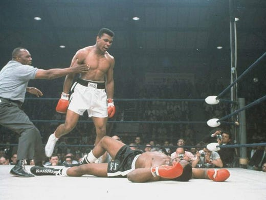 World heavyweight champion Muhammad Ali is held back