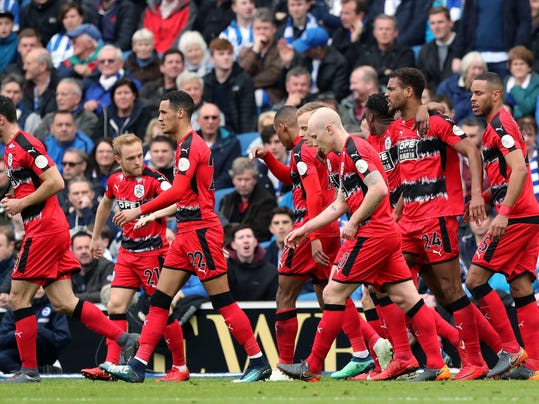 Huddersfield Town's players celebrate scoring their side's first goal of the game  during the English Premier League soccer match between Brighton and Hove Albion and Huddersfield Town at the AMEX Stadium, Brighton, England. Saturday, April 7, 2018. (Gareth Fuller/PA via AP)