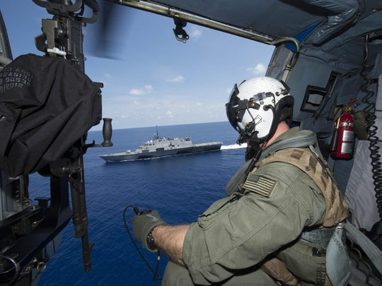 Naval Aircrewman 2nd Class Ian Carpenito observes the littoral combat ship USS Fort Worth as it conducts routine patrols in international waters.