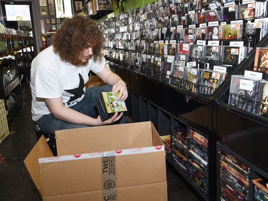 Sales associate Tyler Gerken packs up DVDs at Darkside Records on Main Street in the Town of Poughkeepsie. The Main Street location was scheduled to be open for the last time Tuesday, as Darkside moves to a new location off of Dutchess Turnpike.