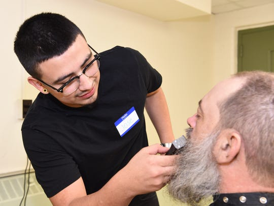 Barber apprentice Jose Lopez cuts Bernie Bainter's hair during the Dutchess Project Connect held on Monday at the Family Partnership Center in the City of Poughkeepsie.  Monday's event provided free haircuts for the homeless in Poughkeepsie, as well as information for a broad range of services available to locals in need.
