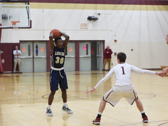 Lourdes' Kevin Townes, left, looks for an open teammate in a game against Arlington last January.