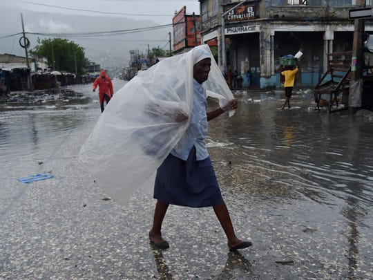 A woman protects herself from the rain with plastic