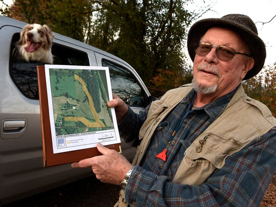 Streams degraded by cows and invasive species could be restored under a proposed environmental development at Neely's Bend. Farmer Steve North, who owns the land, displays an aerial photo of proposed property easements, Monday Nov. 21, 2016, in Nashville, Tenn.