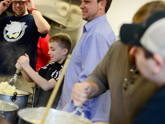 Austin Beats, 11, of East Manchester Township, takes a turn mashing potatoes.