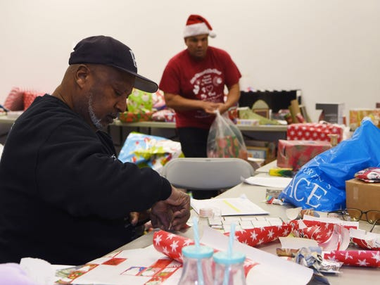 Richie Lawrence, left, a volunteer from the City of Poughkeepsie, helps label and organize gifts before the John Flowers and His Elves Annual Christmas Giving event.