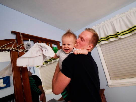 Chris Doemland hugs his son, 11-month-old Sammy, after changing him at their home in West Manchester Township. When Doemland learned he was pre-diabetic, he decided to get healthy for his two kids and wife. Since March he's competed in two triathlons, swam in the Keystone State Games and lost 70 pounds.