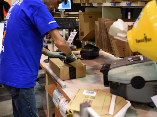 A worker packing an item at the Amazon distribution