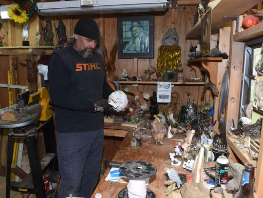 Don Mesuda, a chainsaw carver, in his workshop at his