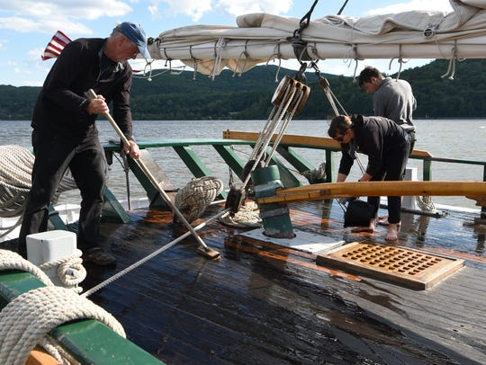Crew members and volunteers scrub the decks while the