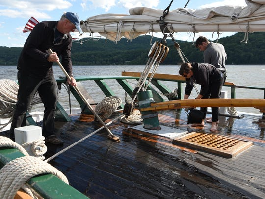 Crew members and volunteers scrub the decks while the ship is docked in Cold Spring.