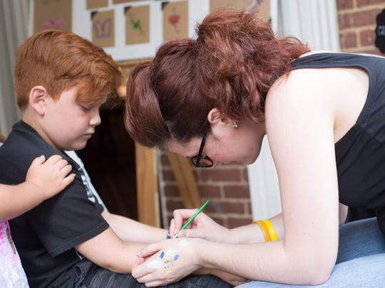 Brittany Fox applies her art to Braydyn Mead during the Rose Mont Renaissance Festival in Gallatin on Saturday, June 17.