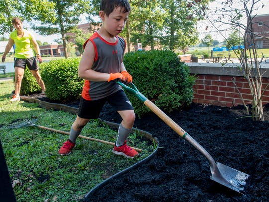 Max Becker, 7, levels the black mulch out in a Henderson