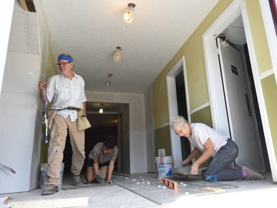 Stacy Tiffin, chairman of the board of directors for the Twin Lakes Playhouse (left), walks by as volunteer Nikki Schlote (middle) and board member Laurel Tiffin (right) install ceramic tiles Friday morning as part of a construction project. The project is already in the final stage.