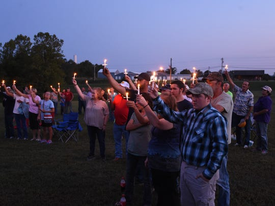 The crowd holds up candles during a ceremony to honor murder victim and junior firefighter Savannah Leckie