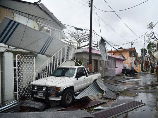 Residents of San Juan, Puerto Rico, deal with damages
