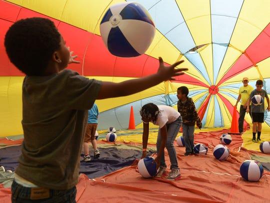 Jalen Bannister, 4, throws around a beach ball inside