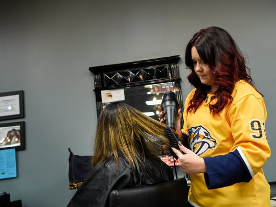 Hairstylist Briley Meeks brushes out Olivia Rodney's hair in Madison, Tenn., Thursday, April 5, 2018.