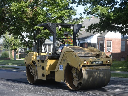 A crew works to finish paving a portion of West Main