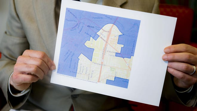 "David Niven, a professor of political science at the University of Cincinnati holds a map demonstrating a gerrymandered Ohio district, April 11, 2019, in Cincinnati. ""The point of this map was to build a seawall against the storm, and it has held,"" Niven said."