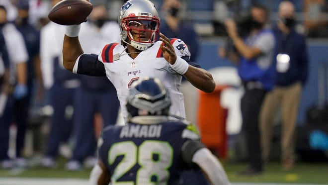Patriots quarterback Cam Newton delivers a pass Sunday night as Seahawks safety Ugo Amadi looks on during the second half in Seattle.