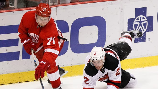 The New Jersey Devils' John Moore, right, tries to steal the puck from the Detroit Red Wings' Dylan Larkin at Joe Louis Arena on Dec. 22, 2015, in Detroit.