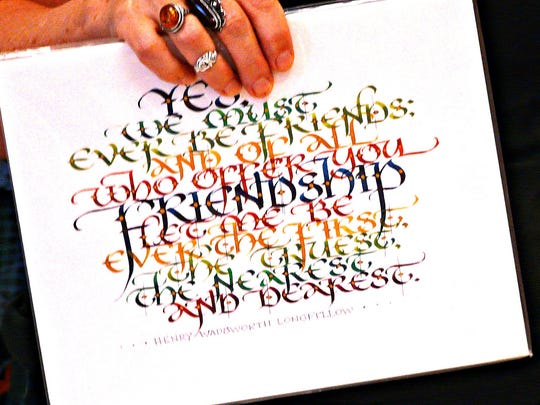 Who says penmanship is dead? Catherine Lent displays a sample of her calligraphy to Del Val High School students.