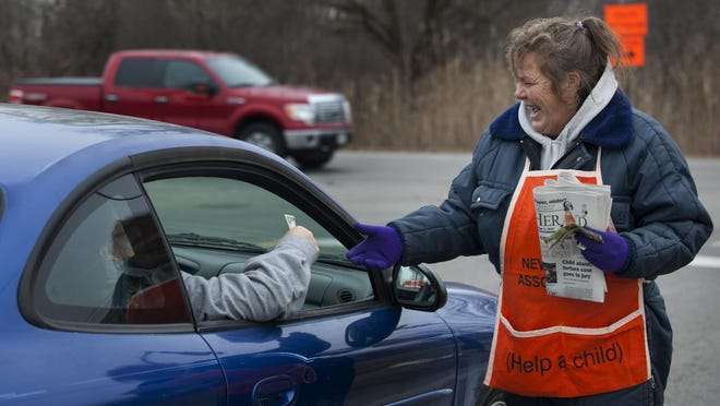 Lisa Towle, of Kimball Township, hawks newspapers to raise money for the Old Newsboys at the corner of Griswold Road and 32nd Street in Port Huron Township.