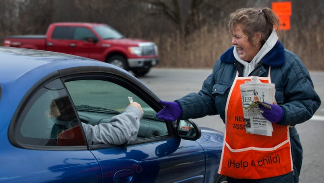 Lisa Towle, of Kimball Township, hawks newspapers to raise money for the Old Newsboys Friday at the corner of Griswold Road and 32nd Street in Port Huron Township.