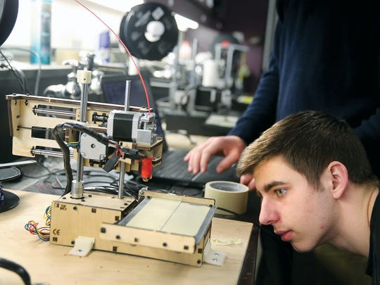 North Kitsap High School engineering student senior Nick Cullen looks closely as he builds a 3D printer.