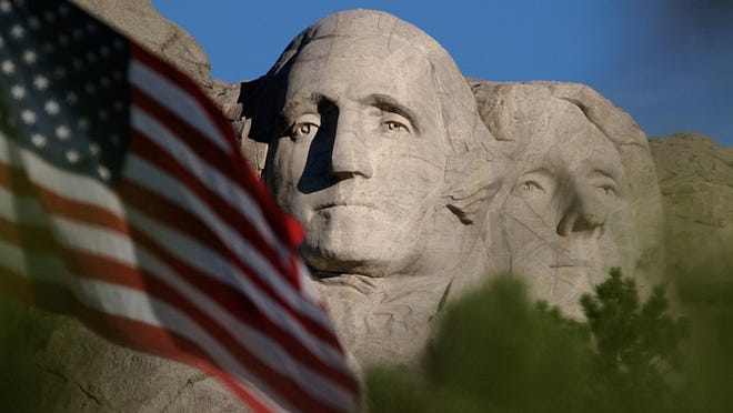 FILE - In this Sept. 11, 2002, file photo, the sun rises on Mt. Rushmore National Memorial near Keystone, S.D. as the flag is flown at half staff in honor of the first anniversary of the Sept. 11 terrorist attacks against the United States.