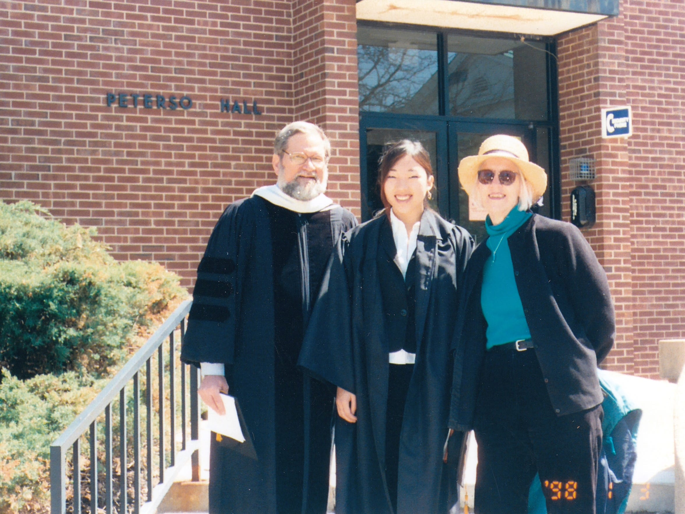 College graduate Joy Fisher shown with her parents,