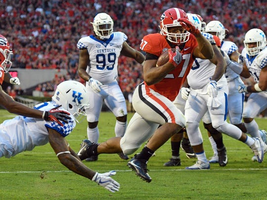 Georgia's Nick Chubb (27) jumps past UK's Derrick Baity (8) to score during their 2017 game at UGA.