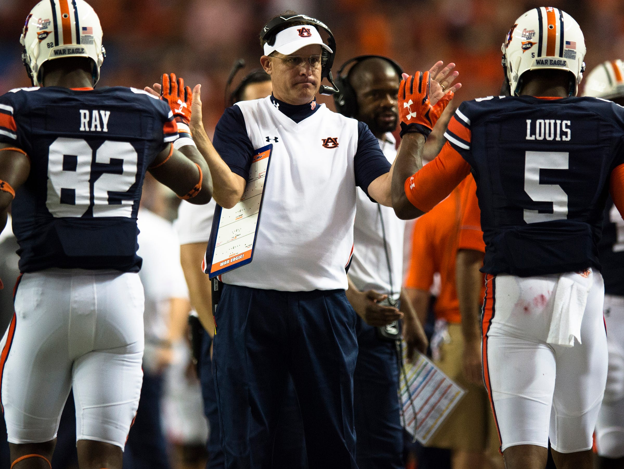 Auburn head coach Gus Malzahn high fives Auburn wide receiver Melvin Ray (82) and Auburn wide receiver Ricardo Louis (5) after Louis scored a touchdown during the NCAA football game between Auburn and Louisville on Saturday, Sept. 5, 2015, in at the Georgia Dome in Atlanta, Ga.