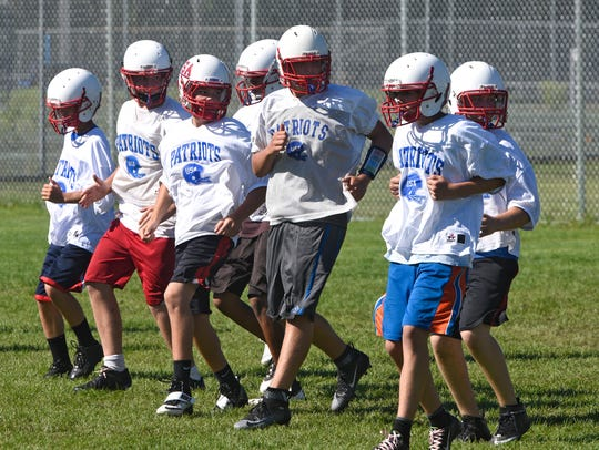 Upsala/Swanville players run backwards during a conditioning