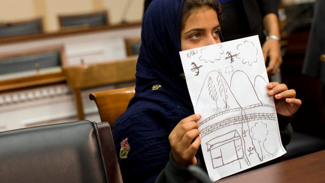 Nine-year-old Nabila Rehman holds a photo with a drawing she made depicting a drone strike that killed her grandmother,