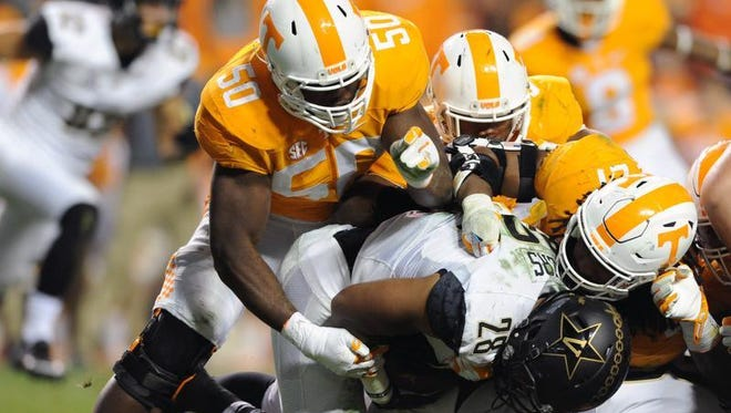 Tennessee defenders stop Vanderbilt running back Dallas Rivers (28) during the second half of an NCAA college football Saturday in Knoxville.