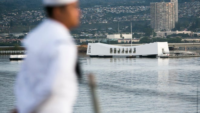 A Navy sailor is seen as the Arleigh Burke-class guided-missile destroyer, the USS Halsey, passes the USS Arizona Memorial, Wednesday, Dec. 7, 2016, in Honolulu. Today marks the 75th anniversary of the surprise Japanese attack on Pearl Harbor initiating the War in the Pacific.