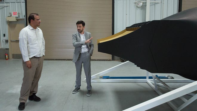 Dumitru Popescu, the CEO and founder of ARCA Space Corp. discusses the new engine ARCA will be testing with Enrique Irigoyen who works at White Sands Missile Range, during an open house of  the new ARCA Space Corp. fabrication hanger and offices Thursday September 14, 2017.