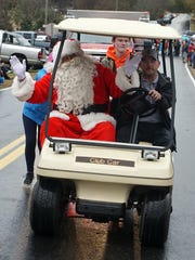 Santa waves to the crowd Sunday as he travels the Denver