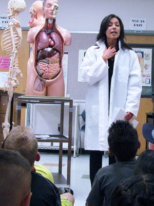 Doña Ana Community College Assistant Professor Sarah Balizan points out the trachea to students at Clyde W. Tombaugh Elementary during Science Day.