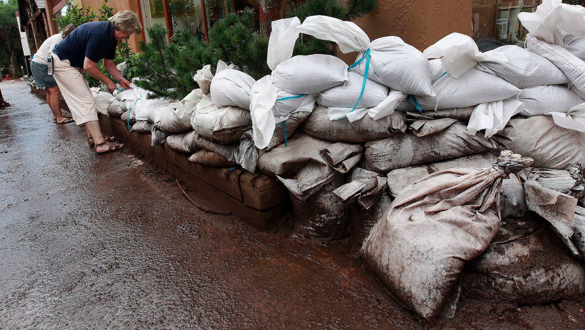 Women sandbag a shop Aug. 12 after a flash flood in Manitou Springs, Colo. A mudslide and flash flood struck the town on Aug. 9 after 1.3 inches of rain fell in an area burned by last year's Waldo Canyon Fire.
