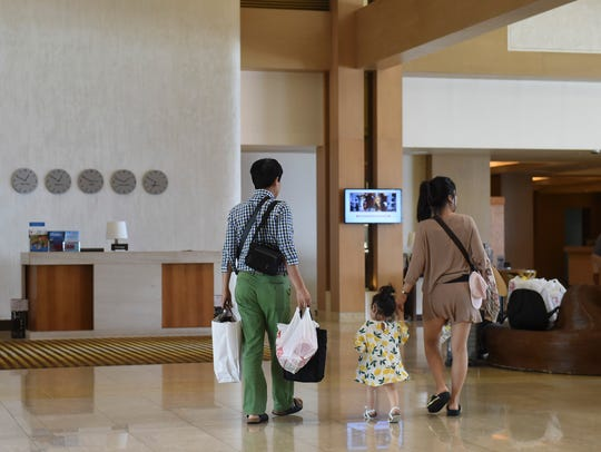 A tourist family walks through the Lotte Hotel Guam