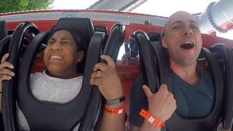 Felecia Wellington Radel and Alex Biese react to the Cyborg Cyber Spin ride at Six Flags Great Adventure in Jackson, NJ.
