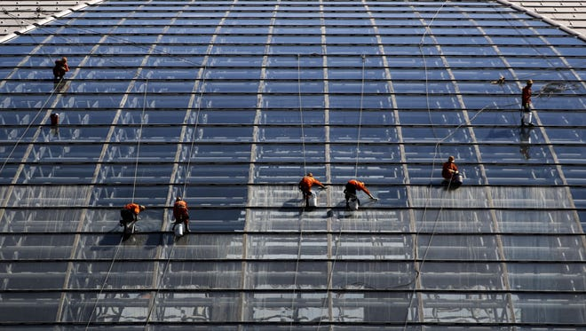 A team of window washers descend on ropes as they clean the titanium dome of the National Centre for the Performing Arts in Beijing.