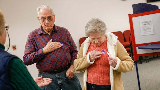 From left, election worker Janet Wood passes stickers to Doyal Humphries and wife Doris Humphries shortly after they cast their votes on Tuesday, March 6, 2018 at Bloomfield City Hall. Under the Local Election Act, Bloomfield may join other municipalities in changing the dates of elections and leaving polling administration to the county clerk's office.