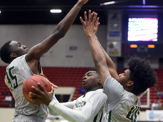 Lincoln's Trinton Bryant (4) splits St. Pete defenders Glenn Miller II (35) and AJ Ford (44) in their class 7A semifinal during the FHSAA Boys Basketball Finals at The Lakeland Center in Lakeland, FL on Thursday February 25, 2016.  St. Pete defeated Lincoln 71-65 to advance to the final.