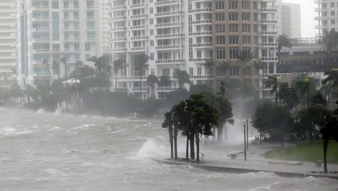 In this Sept. 10 photo, waves crash over a seawall at the mouth of the Miami River from Biscayne Bay, Fla., as Hurricane Irma passes by in Miami. Rising sea levels and fierce storms have failed to stop relentless population growth along U.S. coasts in recent years, a new Associated Press analysis shows.